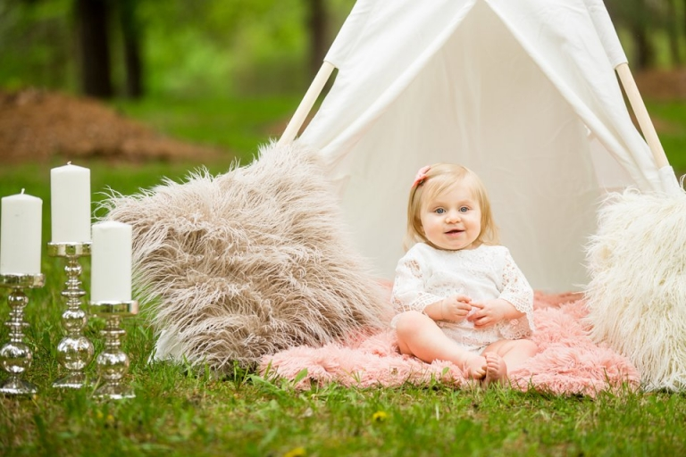 Photographs of a toddler under a teepee with fuzzy pillows